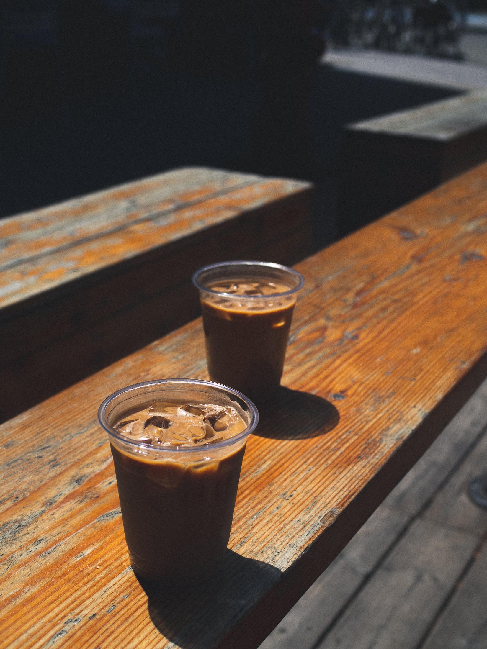 deux cafés glacés posés sur un banc au soleil