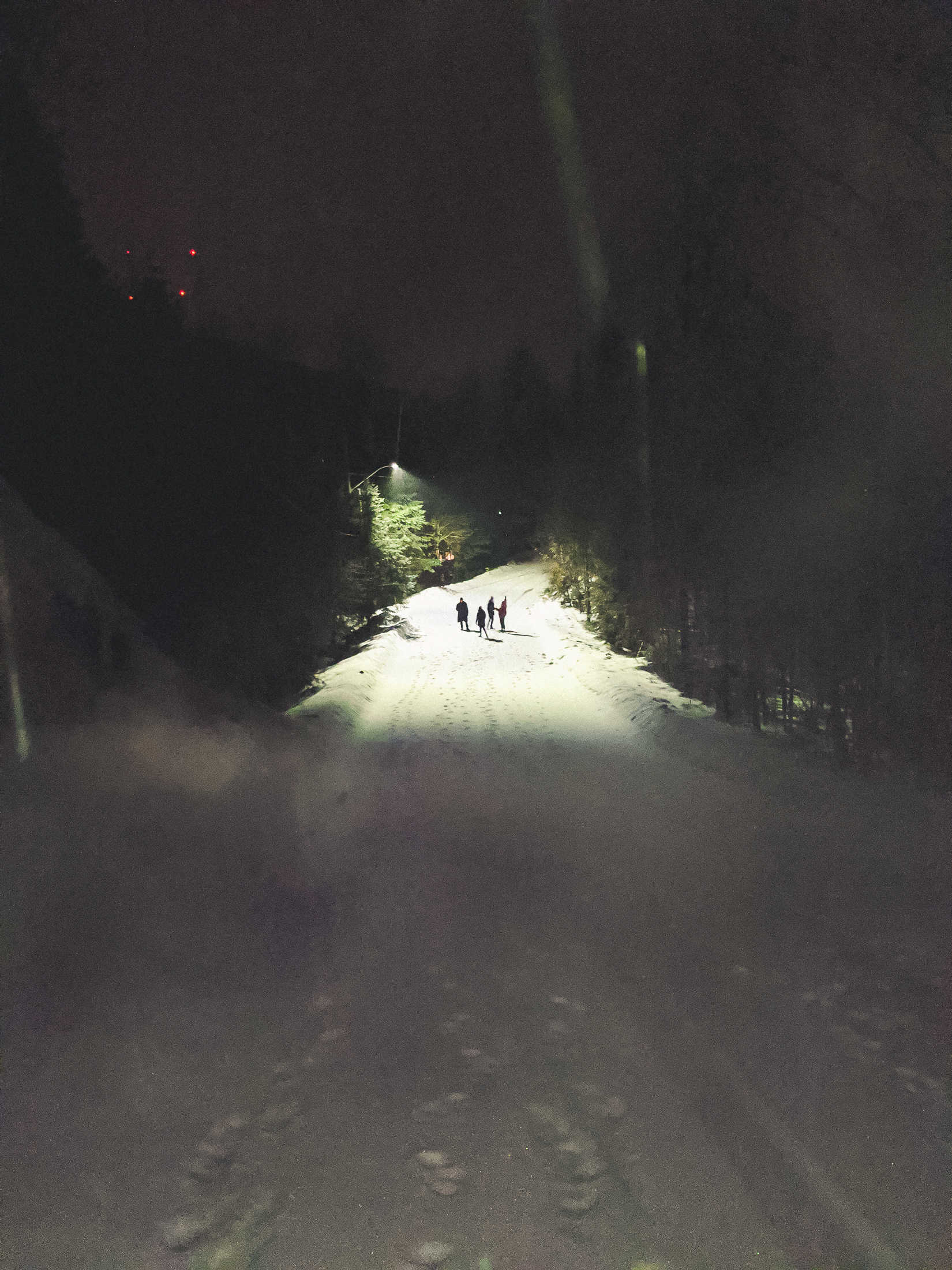 4 personnes au loin dans la neige la nuit