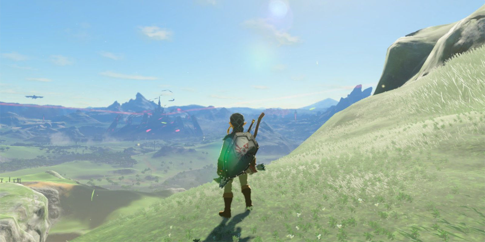 Link stands near a cliff's edge, overlooking the green fields and blue skies of Hyrule. Calamity Gannon's dark magic has corrupted the distant Hyrule Castle, causing inky, black slime to surround its base, and swirling red energy to circle its towers.