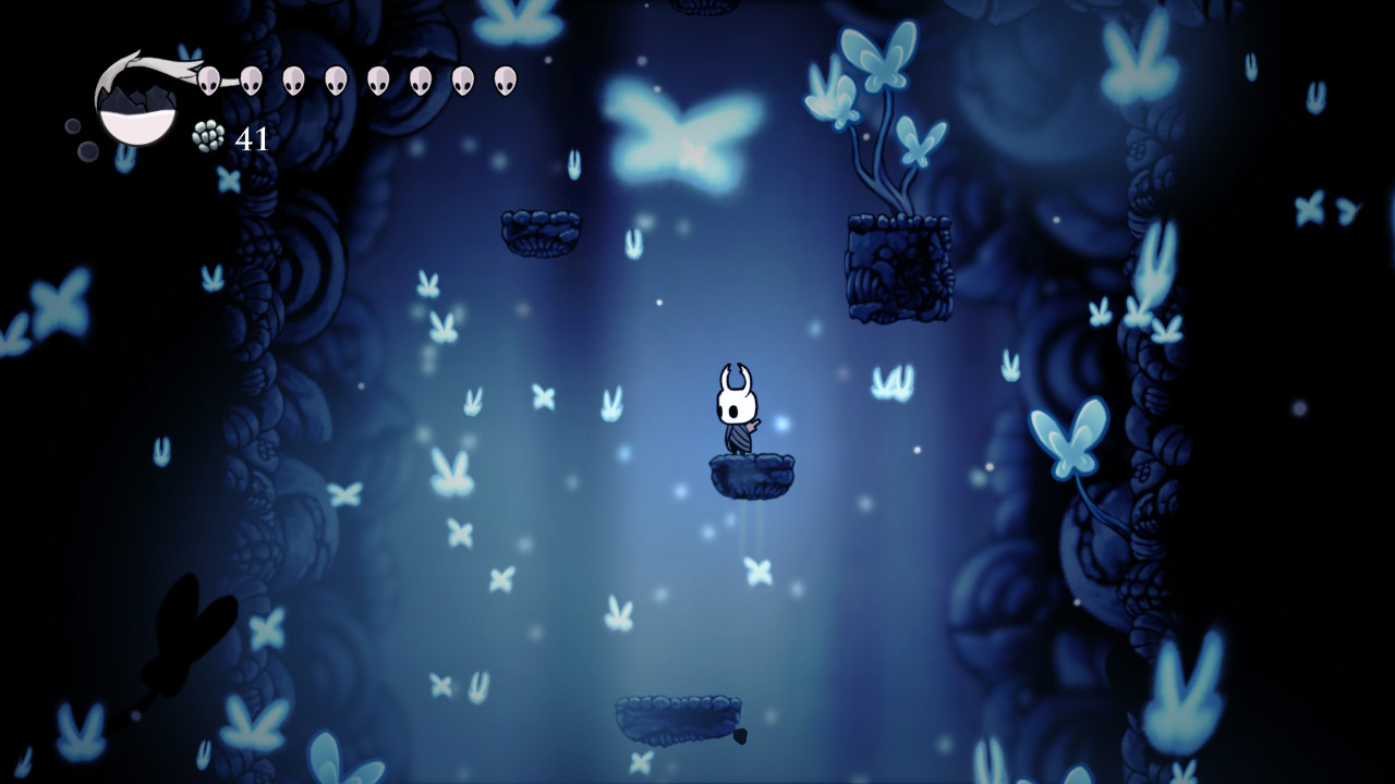 The Wanderer is making its descent through a vast shaft, softly lit in pale blue light. A sea of glowing blue butterflies surround them.