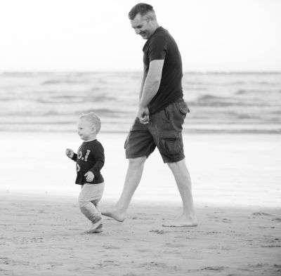 Father and son walking on the beach.