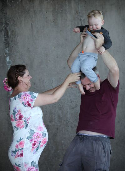 Mom and dad trying to put their toddler on dad's shoulders.