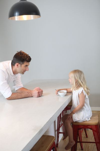 A father having breakfast with his little girl at home.