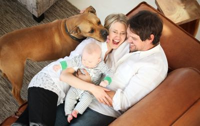 A couple with their baby and their dog at home.