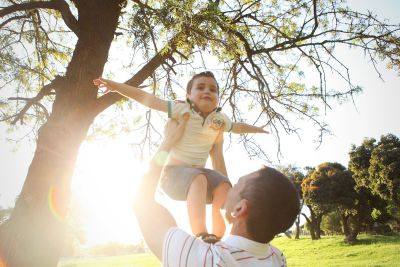 A father holding his son in the air while he pretends to be an aeroplane.