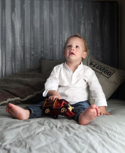 Boy sitting in his room playing with a toy aeroplane.