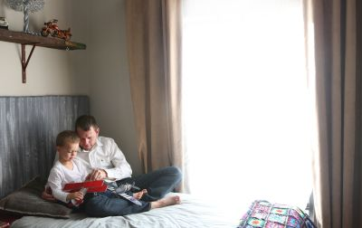 Father and son sitting on the bed.