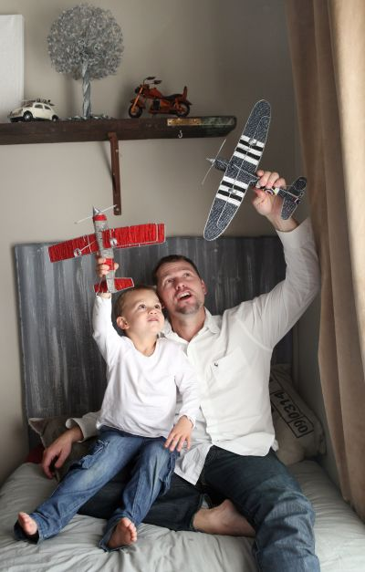 Father and son playing with an aeroplane.