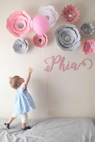 Little girl reaching for a pink balloon.
