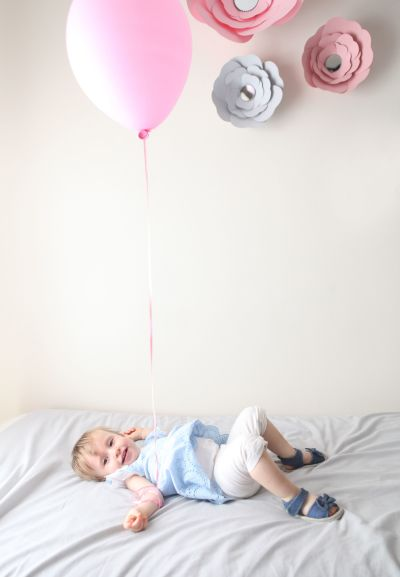 Little girl lying on her back on her bed while holding a pink balloon.