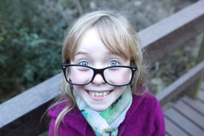 A little girl wearing her sister's glasses.