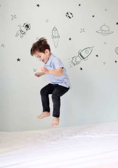 A boy jumping on his bed with space themed wallpaper in the background.
