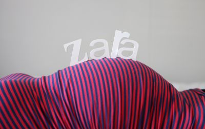"Close up photo of a lady's pregnant belly with block letters spelling ""Zara""  rested on top of her belly."