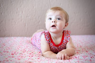 "A beautiful little girl lying on her tummy for ""tummy time""."