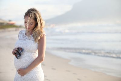A mother to be on the beach during a maternity shoot.