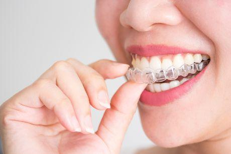 A smiling woman holding invisalign or invisible braces