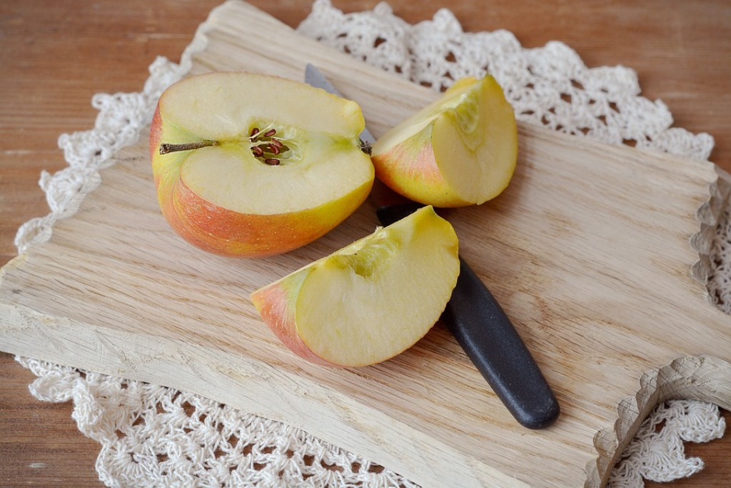 Apple slices on a cut board with knife