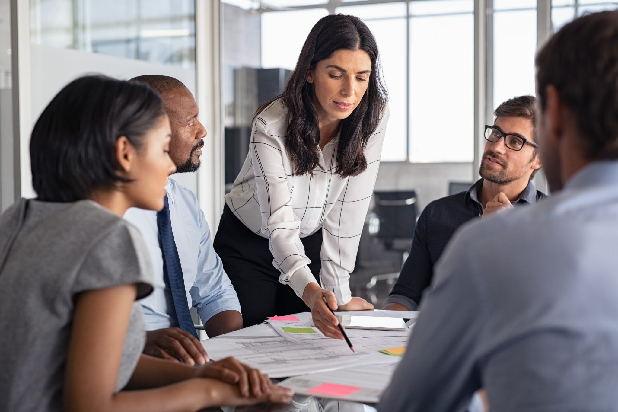 Team of multiethnic architects working on construction plans in meeting room. Engineers and designers discussing project in office. Businesswoman with business team in conference room working on blueprint.