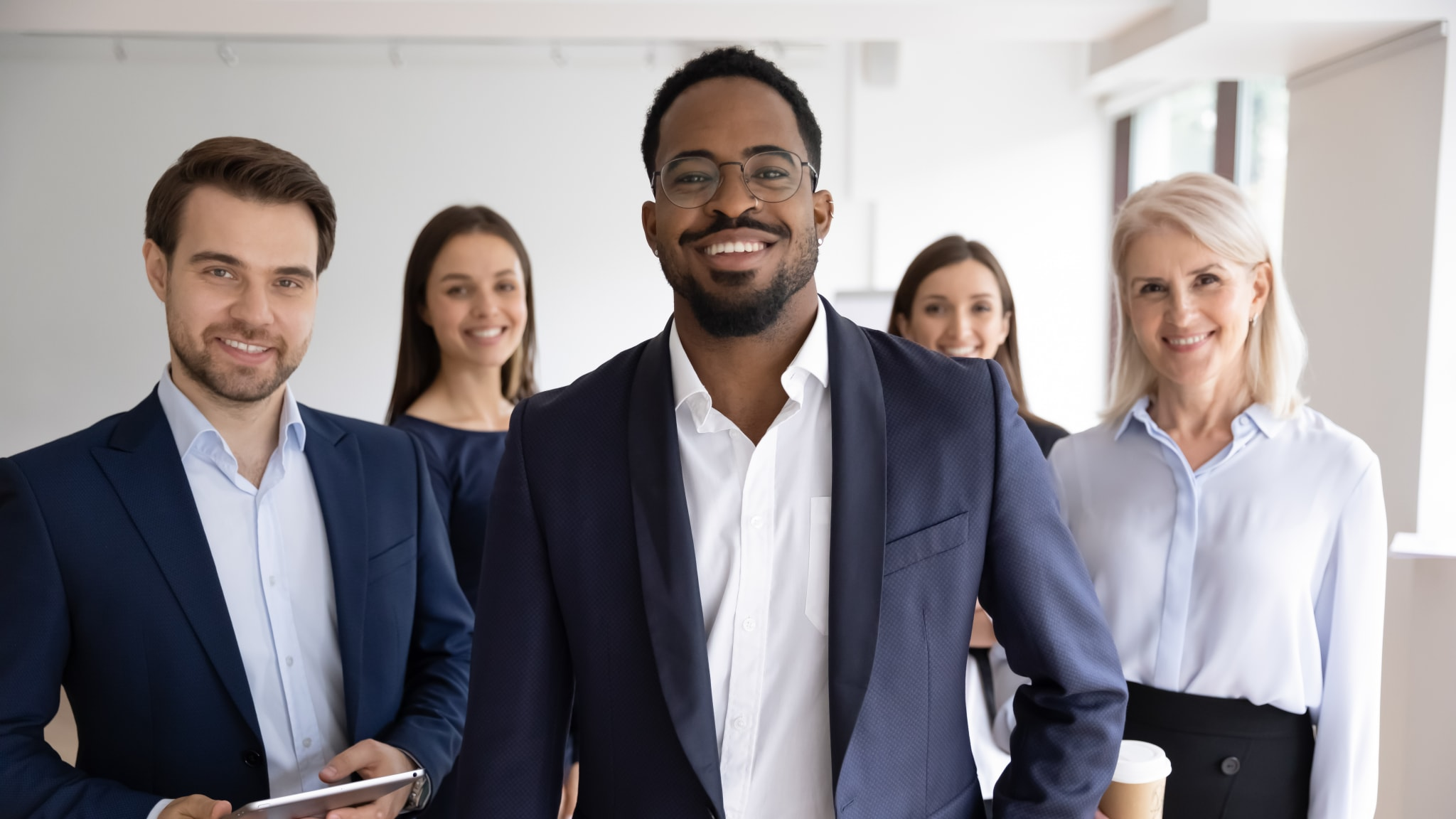 Group portrait of smiling motivated multiracial businesspeople stand show unity and support, happy multiethnic diverse colleagues coworkers posing together in office, teamwork, leadership concept