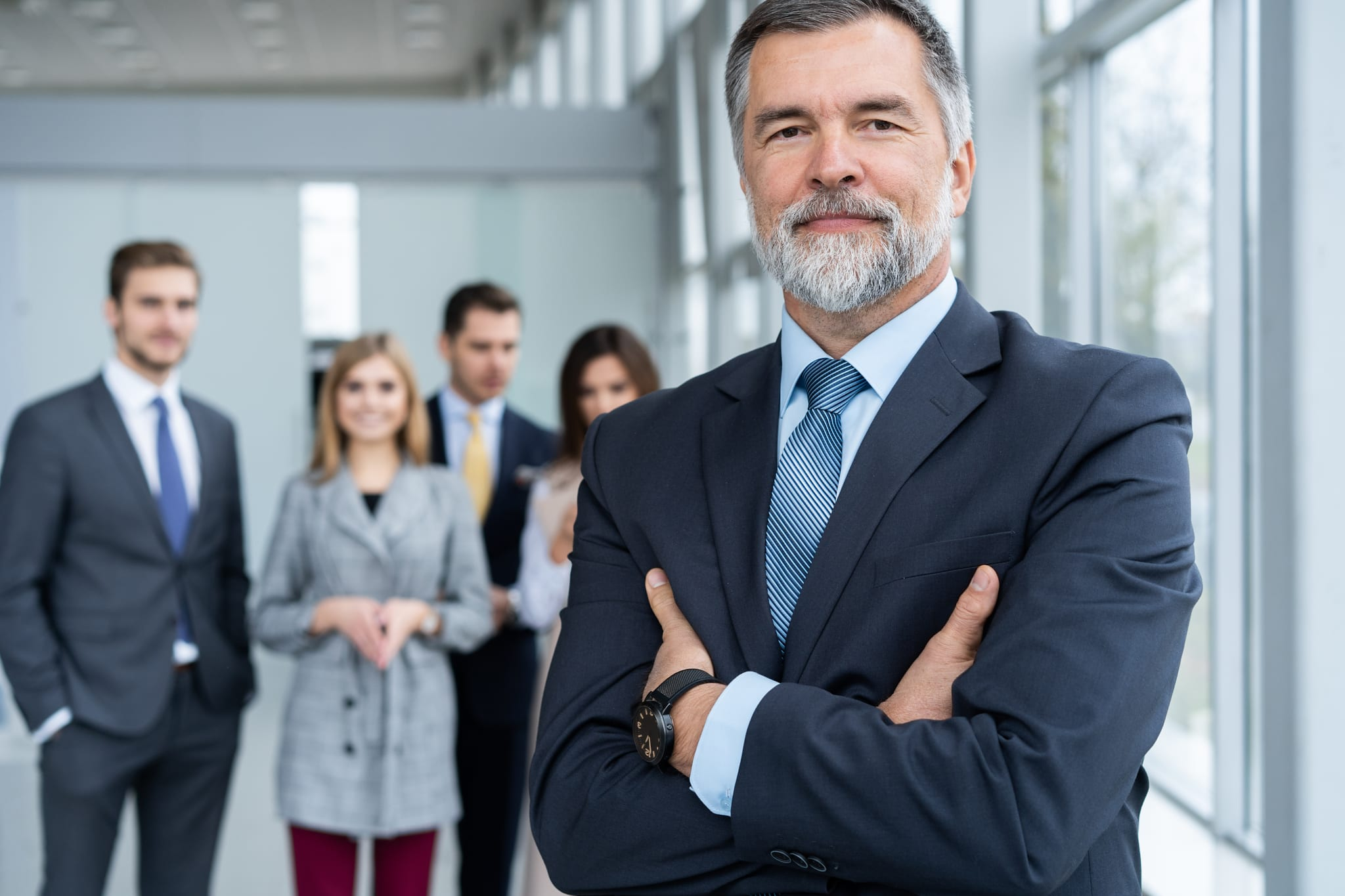 Businessteam in office, Happy Senior Businessman in His Office is standing in front of their team
