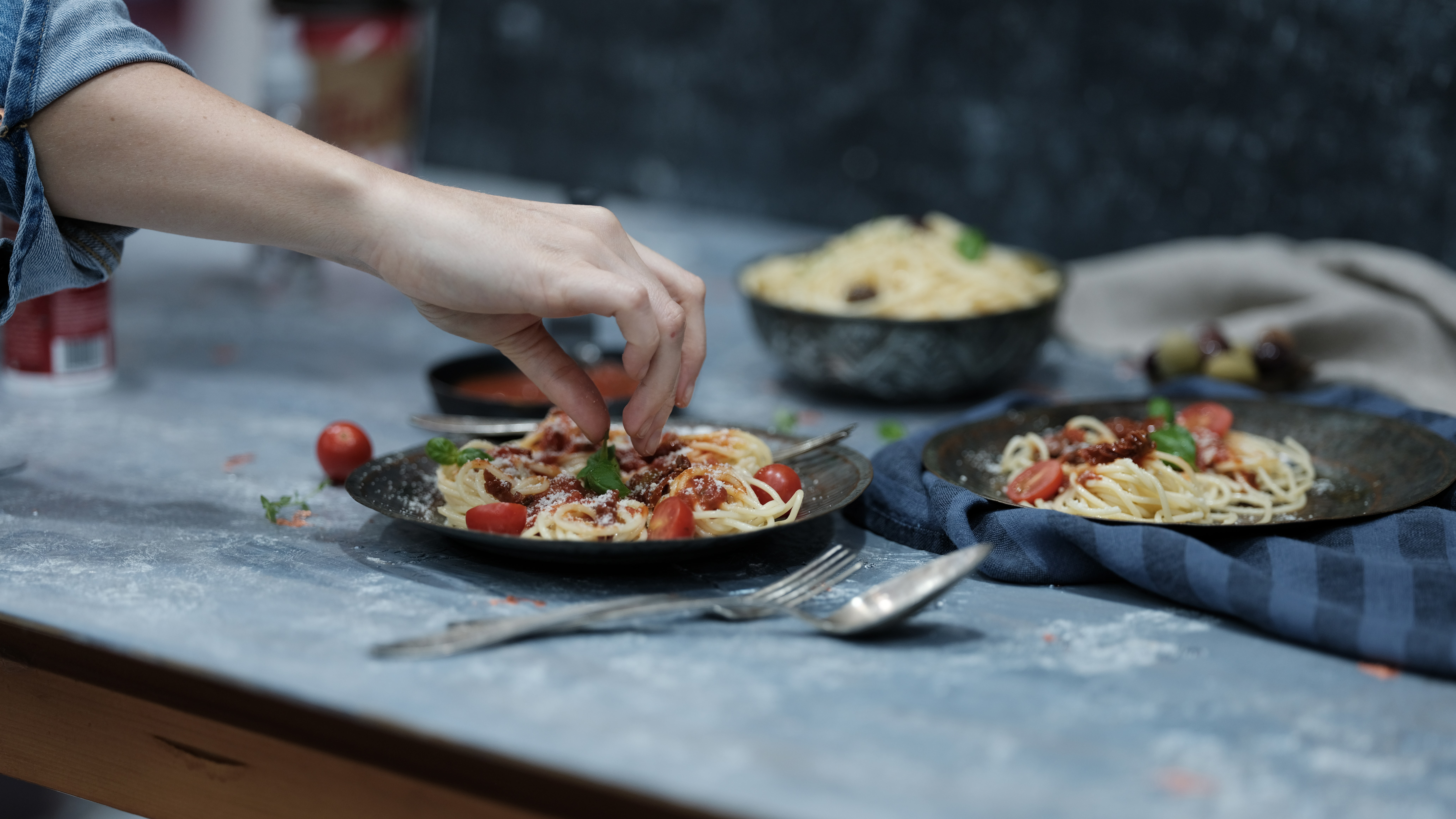 'Chef adding toppings to Pasta'