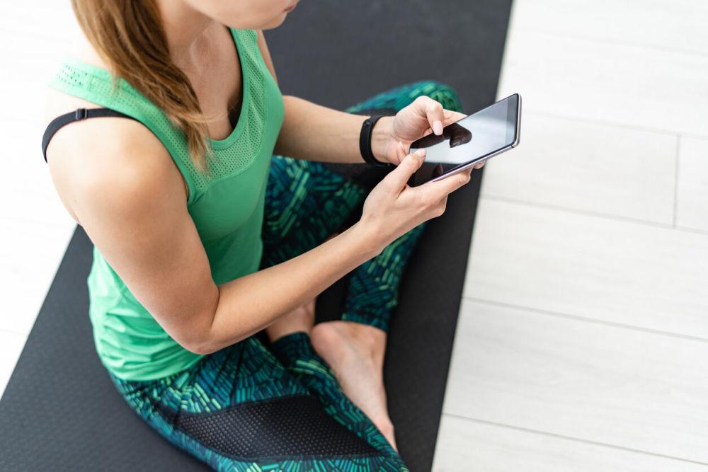 スマートフォンでフィットネスをする女性