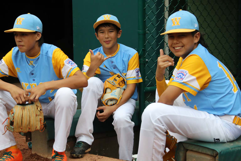 west team sitting by dugout smiling