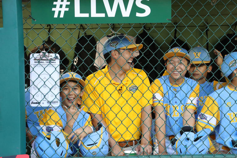 west team in dugout laughing with coach