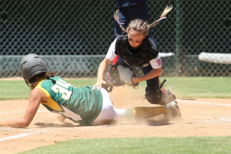 player sliding to home plate as catcher is tagging her