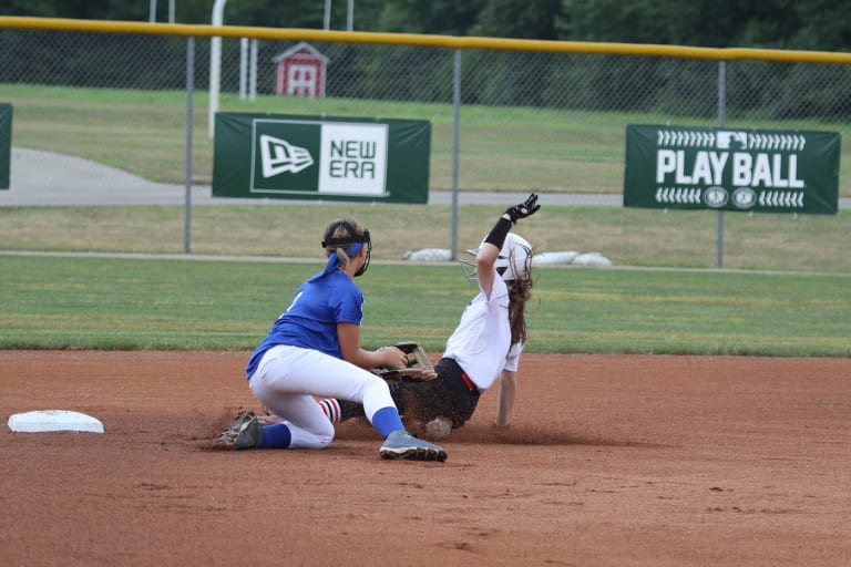 runner sliding into base as fielder tags her