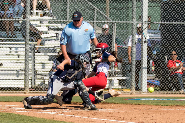 runner sliding into homeplate as catcher tags her with umpire behind