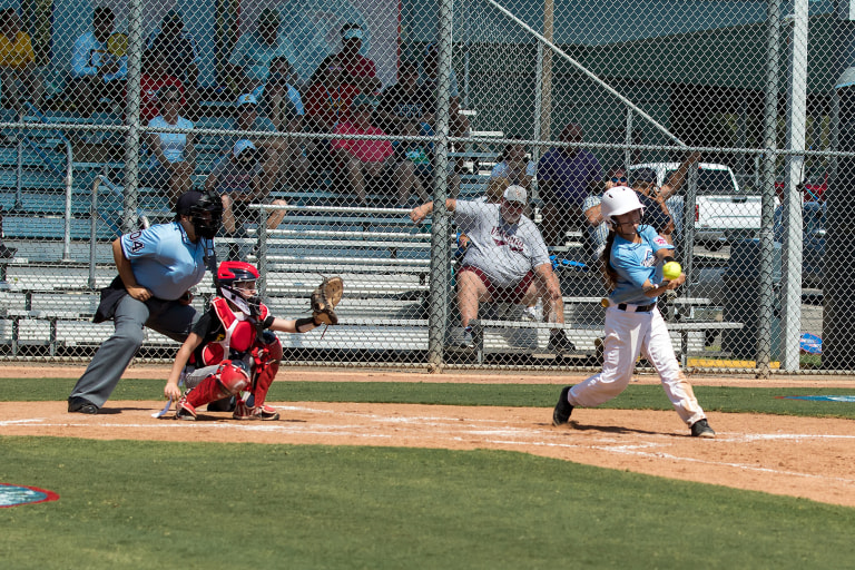 player hitting ball with catcher and umpire behind her