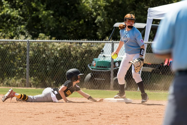 player sliding into base as fielder tags base with ball