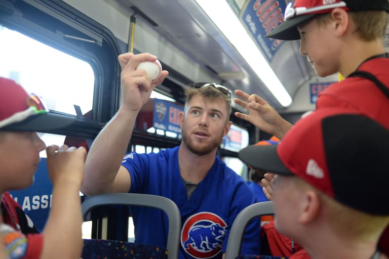 Cubs player giving pitching lessons to Canada players in bus
