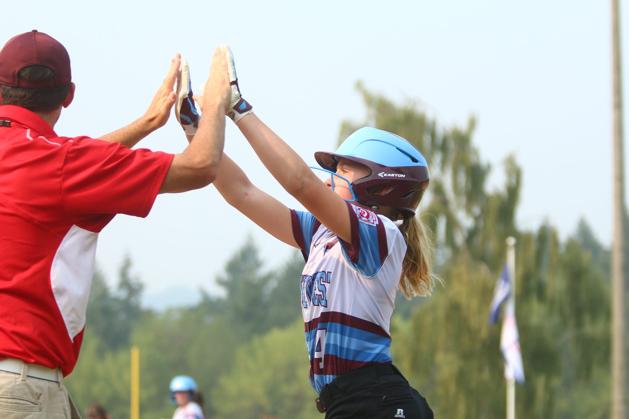 softball player high fiving coach