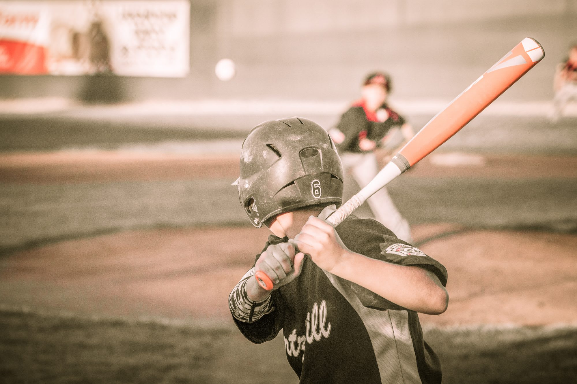 Little League Baseball player swings at pitch