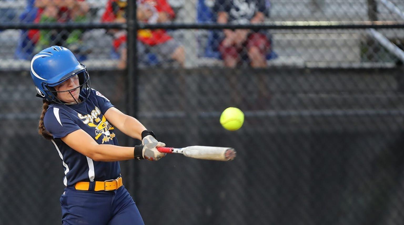 A softball batter swinging the bat