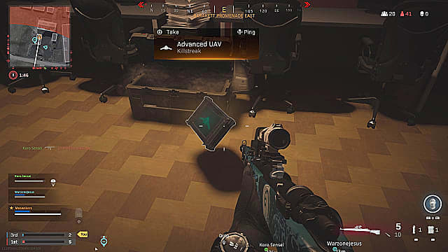 A player holding a marksman rifle, looking at an advanced UAV killstreak floating on the floor near a crate.