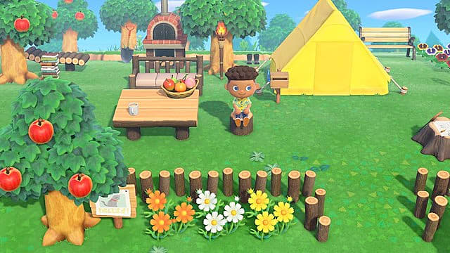 Sitting by a yellow tent and table in Animal Crossing New Horizons.