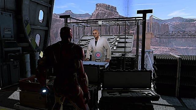 Iron Man standing in front of Sidney Levine's shop in the hangar of the Helicarrier.