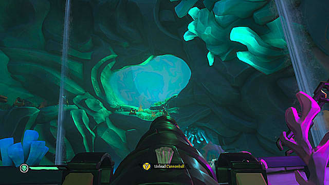 A pirate ship cannon aimed at a large opening in the cave ceiling.