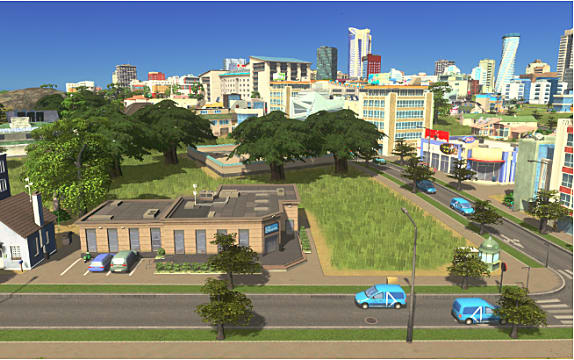 Blue cars drive through an intersection next to a commercial district with mid-tier buildings