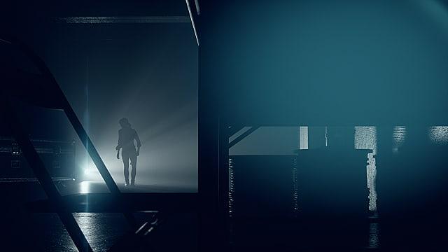 The silhouette of Jess Faden walking toward a light in a dark warehouse.