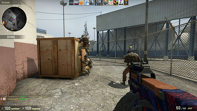 two players climb a large wooden crate while the other two keep watch in Counter-Strike: Global Offensive
