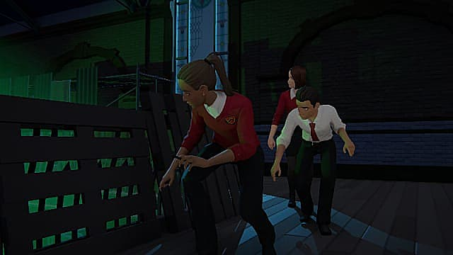 Donna, wearing a red vest and black pants, crouching behind pallets alongside another man and woman