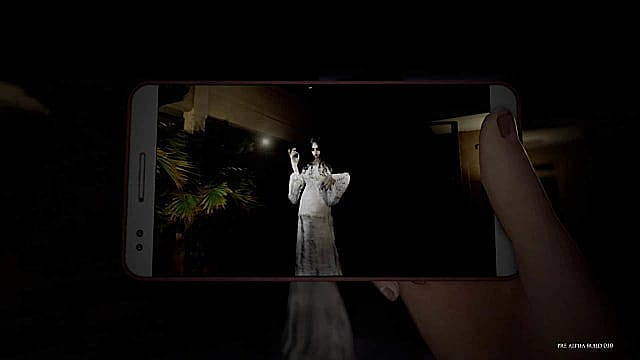 A cellphone captures a creepy image of a white angel-like being in DreadOut 2.