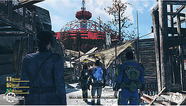 A group of four vault dwellers walk into a settlement with broken shacks and a red tower