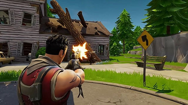 A male Fortnite player with spiked hair shoots a handgun at a running player near a broken down house