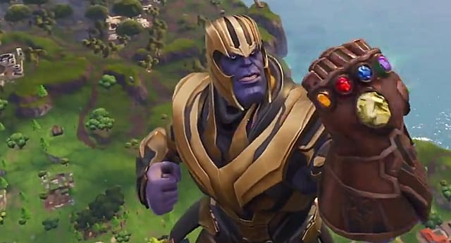 Thanos float above the Fortnite map holding the Infinity Gauntlet in front of his face