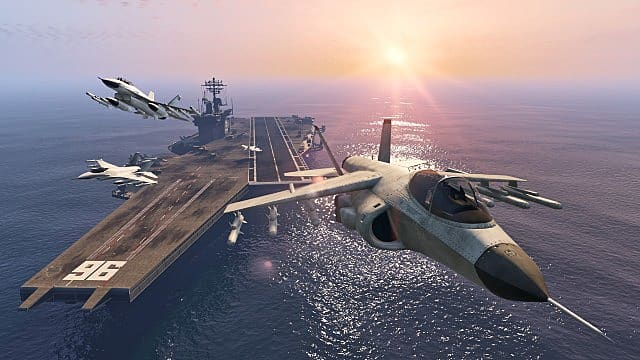 Three fighter jets taking off from an aircraft carrier in the ocean.